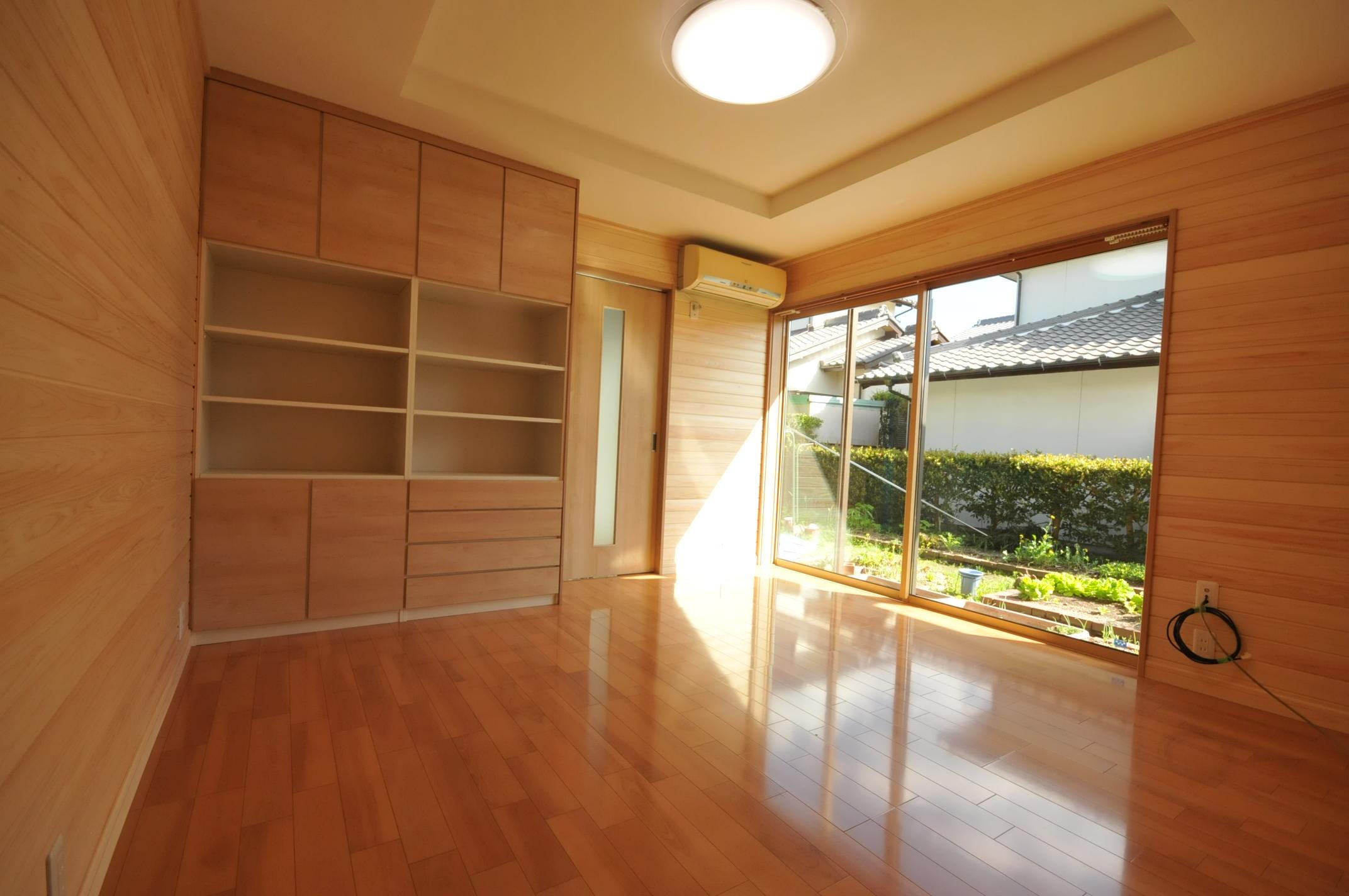 【居間】床には高性能断熱材充填・サッシ交換・壁の仕上げ材は無垢のヒノキ羽目板。パナソニック製の収納棚設置。